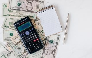 cash, calculator, and notepad